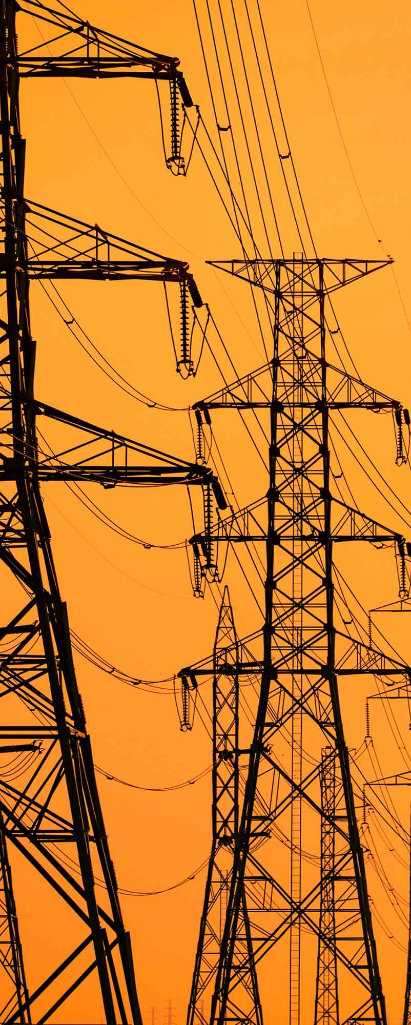 High voltage electric pole and transmission lines in the evening. Electricity pylons at sunset. Power and energy. Energy conservation. High voltage grid tower with wire cable at distribution station.